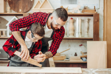 Caucasian bearded father embracing his son and helps to use plane while working with wood