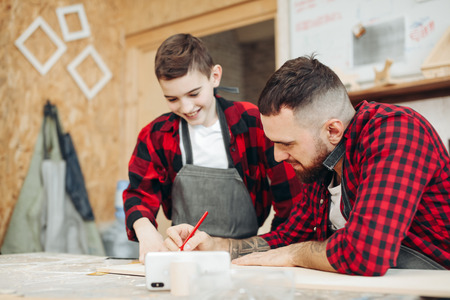 Focused craftsman and his little follower boy are measuring wood using a ruler and pencil in the workshop. Adult man compares the correct markup on wooden plank with the drawing in the phone Stock Photo
