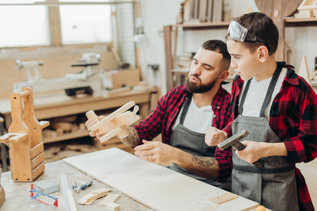 Focused male teacher and his little male pupil making by hand a DIY wooden toy - airplane in carpentry workshop. Stock Photo