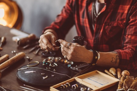 Jeweler working with chain in the workshop, close up cropped photo. talented man repairing the necklace for the client