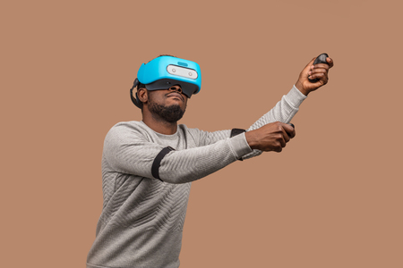 African american male gamer in white pullover and virtual reality headset is meeting new technologies of the future, playing video game, gesturing with his hands as he playing tennis Stock Photo