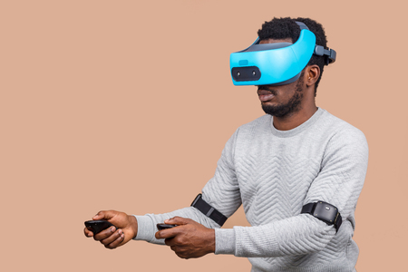 Virtual reality technology is constantly making huge advances. African casually dressed man trying on VR glasses isolated over beige background