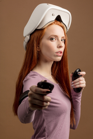Redhead young female student with raised switched off VR goggles on head, looking at camera, standing in fighting stance, holding controllers in hands . Technology, science, innovation concept. Banco de Imagens