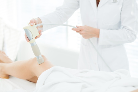 Closeup portrait female long legs getting rf-lifting in a cosmetological clinic, tightening the skin and improving skin turgor. Hardware cosmetology. Body care. Non surgical body sculpting.