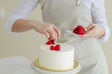 woman creating a beautiful cake. close up cropped photo, professional chefs skills