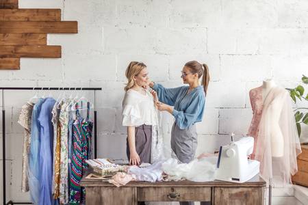 Young female dressmaker taking measurements of a blonde woman to design new clothes in tailoring workshop. Banco de Imagens