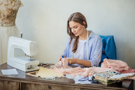 Caucasian concentrated seamstress cutting pink lace fabric, sitting at her workplace with tailor s accessories and sewing mashine in studio