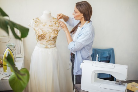 Young caucasian seamstress inserts needles into a lace wedding dress dressed on dummy. Creation of fashion clothes in fashion studio.