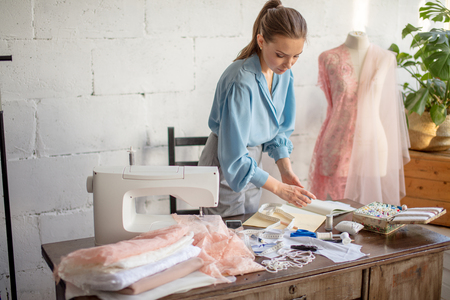 Pleasantly looking wearing ponytail is sitting at her worktable with laid tailoring equipment, containers full of thread spools, thinking of color while choosing thread for sewing.
