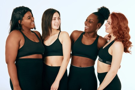 Group of women of different race, figure and size in sportswear standing together, chatting and laughing against white background. 免版税图像