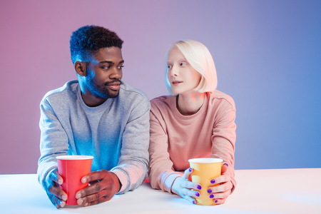 multiracial young woman and a young man seating at a coffee table isolated on blue ground, love, family, friendship