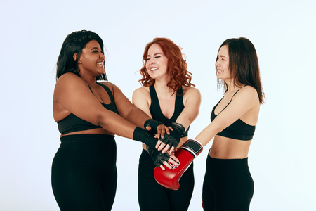 Three multicultural diverse girlfriends giving high five with red boxing gloves and black mitts isolated over white background