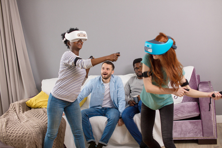 Two multiracial young women dancing wearing virtual reality glasses at home while their boyfriends sitting on couch and smiling, enjoying the action