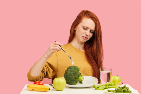 Redhead frustrated confused disgusted displeased female model makes a wry face refusing to eat broccoli and veg healthy food sitting at table over pink background. Eating disorders and mental health