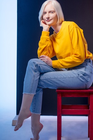 positive charming blond woman sitting on a stool isolated on blue background, studio shot , beauty, free time, spare time