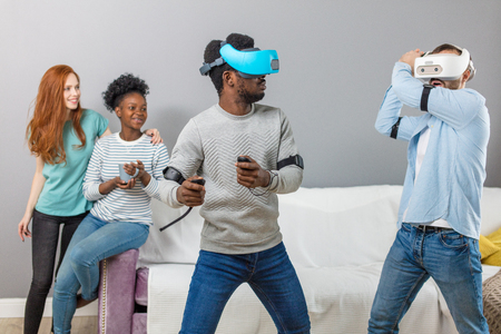 Group of multiracial male and female students playing virtual game using vr goggles, having fun together ay home - Virtual omg reality and portable digital technologies