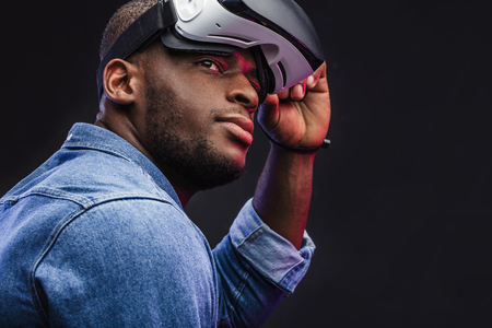 3d technology, virtual reality, gaming, entertainment and people concept - confident dark skinned man taking off virtual reality headset or 3d glasses while playing game over black background