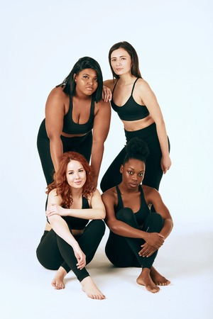 Group of four women of different race, figure type and size in sports outfit posing together over white background.