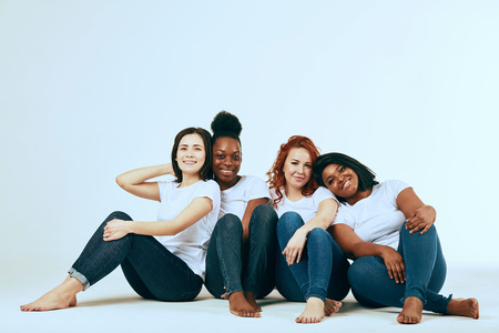 University students posing in studio in skinny jeans and white t-shitrs. All women are natural and different in their common beauty, having diverse skin, hairstyle and body weight, happy in youth