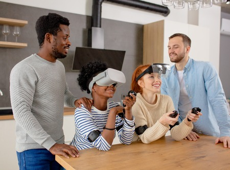 Virtual battle of two multiracial teams, consisting of loving african and caucasian couples playing in virtual reality game Guys support and teach their girls in vision headsets, standing near in room