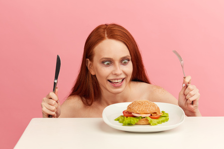Diet failure of emaciated skinny redhead woman suffering from anarexia with greedy bugged eyes being ready to eat fast food hamberger. Unhealthy lifestyle bulimia concept. Junk meal leads