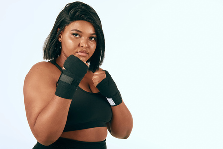 Plump african american mixed race woman showing her confidence while training in studio over white background. Fitness, Sport, Plus-size Model and Body Positive