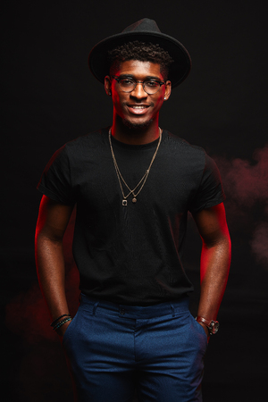 Portrait of handsome young african DJ or jazz musician in creative hat in black t-shirt on dark background Stock fotó