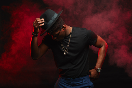 Portrait of happy dark skinned young male dancer with stylish hat, dressed in casual black t shirt, moving isolated over red smoky background. Satisfied African American man in high spirit.