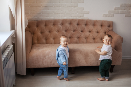 Two adorable infant boys of one year old, standing near vintage sofa at living room, happy smiling learn to walk