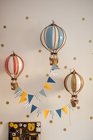 Creative lamps made as colourful air balloons against white background in cozy kid playroom with busy board