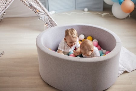 Two happy cute one year old infant boys are playing with colourful balls in a dry pool. Happy Birthday in Shopping Mall Playroom