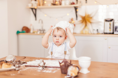 Infant cook baby portrait wearing chef hat looking at camera with funny confident expression. Male toddler sits at table, keeping his Chef s hat on head Banque d'images