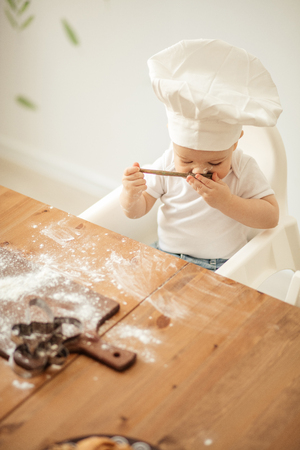 Baby Chef in white Cook hat and t-shirt sitting at table with wooden cutting board, soiled with flour playing with a spoon in the kitchen.