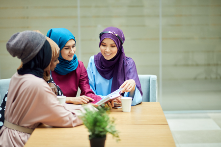 Photo of a happy muslim multiethnic girls students discussing book, sitting at table with take-away tea in colledge hall.