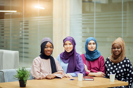 Group of beautiful young muslim business women wearing hijabs of different colour, are sharing info, sitting together at table in business centre