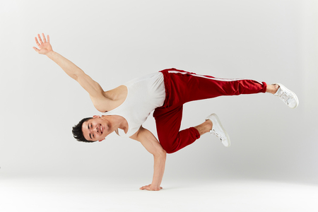Stylish dressed in red sportswear asian personal break dancer trainer doing handstand on white background