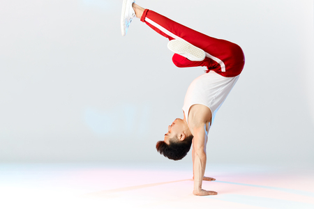 Asian Bboy standing in freeze stunt upside down balancing in air with legs - Street artist breakdancing indoors isolated in studio over white background