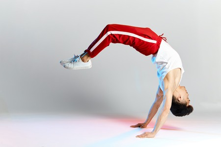 Free style dancer in red sports trousers doing some acrobatic stunts dancing break dance isolated over white studio background