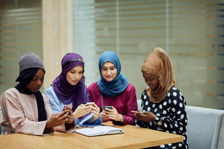 Asian Islamic women in bright hijabs sharing info from smartphone during their visit a seminar at education centre Stock Photo