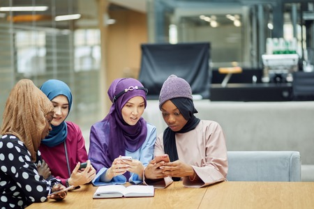 Arabian young fashionably dressed in muslim clothes women watching on cellphone musical video clip standing together at shopping mall- Millennials, generation z and technology concept