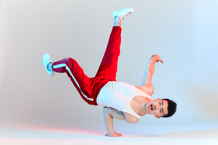 Isolated Korean hip hop male break dancer dancing on white background, performing Air Chair element of downrock breakdance