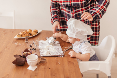 Adorable little baker covered with flour, wearing white Chef s hat, playing with Mom s kitchen tableware sitting with spoon in hands at table.