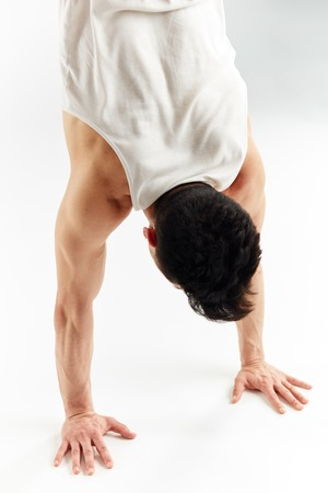Young man in red sweatpants doing a handstand on stretched hands on white background