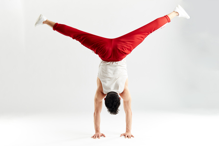 Young man in red sweatpants doing a handstand on stretched hands with splitted out leggs on white background