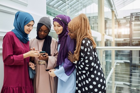 Group of multiracial muslim businesswoman chatting, checking newsfeed on smartphone while having break, standing at business centre Stock Photo