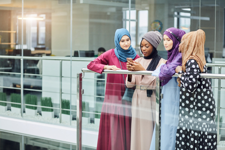 Couple young business muslim female entrepreneurs using smart phone contact with partner together in modern business centre , Muslim business people success concept, co-working teamwork concept