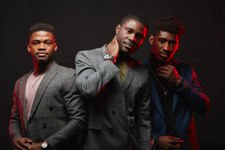 Positive african ethnicity businessmen, well-dressed business partners wearing stylish suits looking at camera isolated in studio. Business Apparel, Fashion and Style, Mens Formal Clothing Stok Fotoğraf
