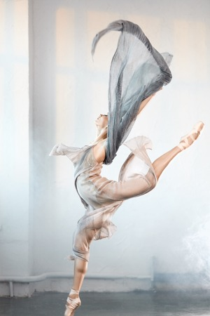 young ballet dancer wearing blue-grey transparent clothes and pointe has incredible grace, lightness and flexibility jumping on the stage with flying fabric and smoke effect