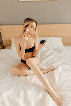 Morning routine make-up. Sexy blonde female applying dry powder foundation looking in mirror sitting in black lingerie on bed