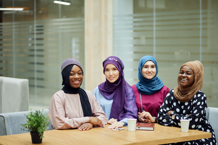 Portrait of multiracial group of muslim women dressed in smart national clothes sitting at table in the business centre and posing for photo. Social diversity, friendship.